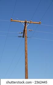 An old telephone pole against a blue sky