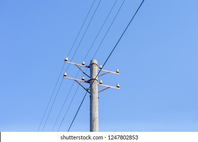 Old telephone pole with wires against a clear sky