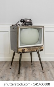 Old Television with 4 legs in the corner of vintage room and a black old telephone on it