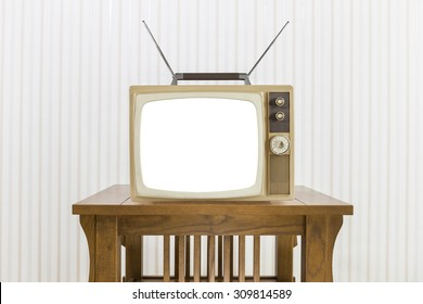 Old television with antenna on wood table with cut out screen.