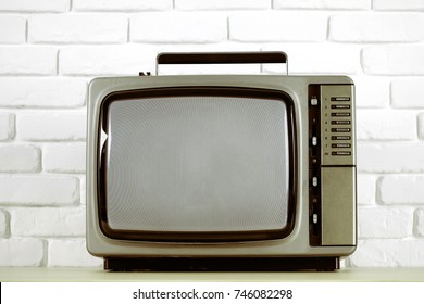 Old television on a white brick wall background.Vintage styls color .