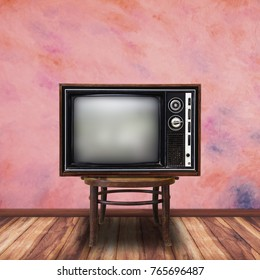 Old television on wood chair in vintage room background.