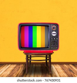 Old television on wood chair in yellow room background.