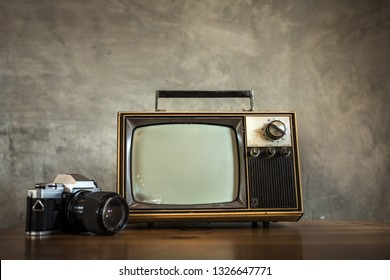 Old television with retro camera on wooden table on concrete wall background, Decorated in coffee shop. Vintage TV