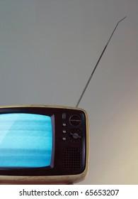 Old televison isolated on greyish background.