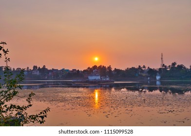 Old temple surrounded by lake. Brahma Hindu temple in Bhubaneswar, Odisha, India. old temples against sunrise sunset glow and sun burst in the background. Warm morning colour tone. Water reflection.