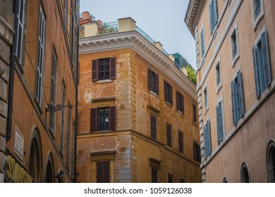 Old tenements in Rome, orange color of facades, windows with shutters