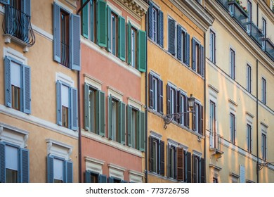 Old tenements in Rome, orange, yellow and red colors of facades, windows with shutters