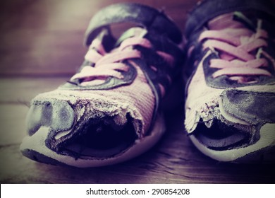 Old tennis or athletic running shoes with holes in them