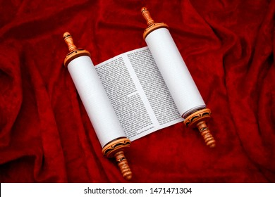 The Old Testament text, Jewish temple or synagogue, religious parchment scroll and the Judaic religion concept theme with the holy Torah open on red velvet background