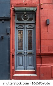 old textural door in grey and  fragment of  house facade in red