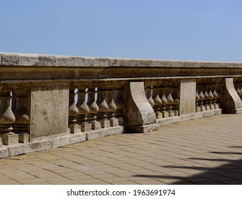 Old textured beige stone low parapet guard wall. blue sky. abstract deminishing perspective view. yellow tile flooring. exterior terrace and observation deck structure.