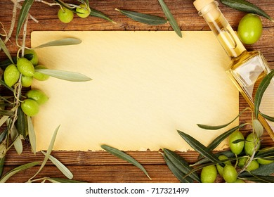 old textured paper surrounded by olives on branches and olive oil for backgrounds