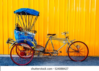 Old thai Cycle rickshaw/ Trishaws against yellow wall on background. colorful and useful for travel concept.
