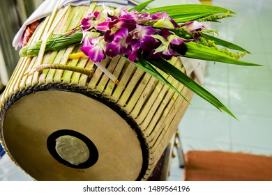 Old Thai traditional drum with purple orchid bouquet on top.