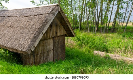 Old thatched hut in Biharugra next to the fishpond. The hut is surrounded by greenery - Biharugra, Bekes county, Hungary, May 2020, bekesstock, csabaprog