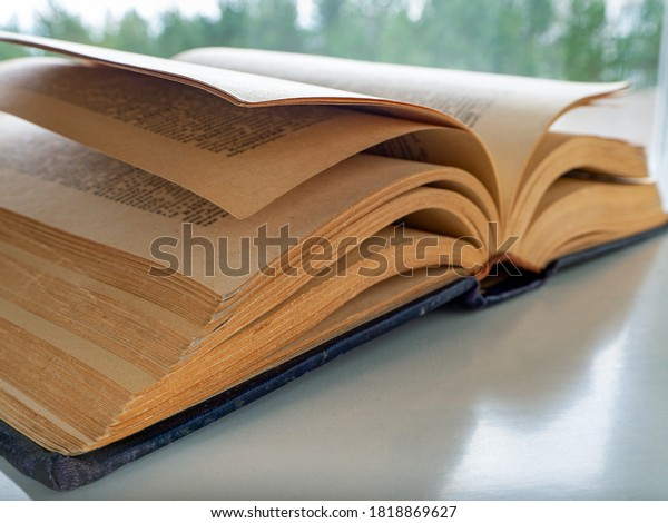 An old thick book is open and lies diagonally on a light table. Background with a book for libraries, education, scientific work, university.