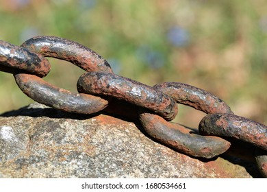Old thick rusty chain of heavy iron close up, placed on a rock with blurred background