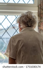 Old thin grey haired old lady stands and looks out of a diamond leaded window to the world outside. The lonliness and isolation of Covid-19 shielding. The houses across the road are out of focus.