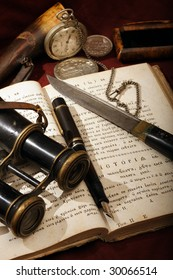 Old things placed on an open ancient cyrillic book. Objects include: a Montblanc pen, a watch, a field-glasses, a knife and other.