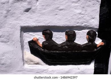 Old three men in a boat mottif in a wall, New Abbey, Scotland