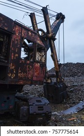 the old thrown excavator covered with rust in the middle of a garbage can, against the background of the dark evening sky