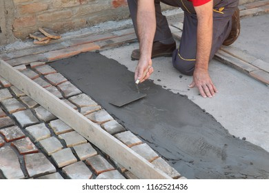 Old tiles recycling, making terrace or pavement using tile pieces,  workers hand spreading mortar or tile adhesive using trowel
