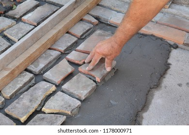 Old tiles recycling, terrace or pavement making, using tile pieces mortar and tile adhesive, workers hand placing piece