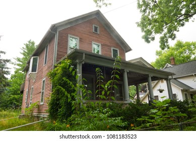 An old timber house with overgrown plants in the foreground in Ann Arbor, Michigan, United States.