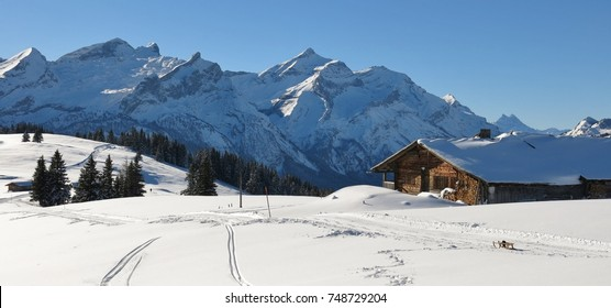 Old timber hut and snow covered mountain Range. Mountains Schlauchhorn and Oldenhorn. Winter scene near Gstaad, Switzerland.