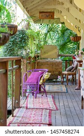 An old timber verandah from yesteryear filled with vintage furniture of a bygone era