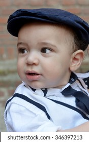 old time style portrait of a baby boy wearing a dark blue cap  white shirt and knitted west looking away from the camera