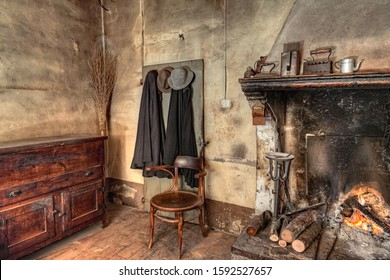 old times farmhouse - interior of an old country house with fireplace, kitchen cupboard, ancient mantles and straw broom