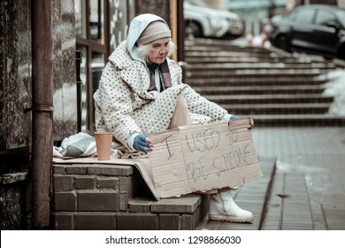 Old times. Sad aged woman thinking about her previous life while sitting on the street