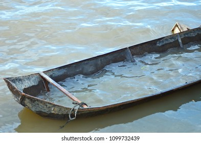 An old tin boat is half-filled with water and moored on a muddy river. The scene is deserted. The boat appears about to sink.