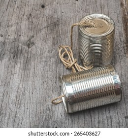 old tin can phone on wood texture board