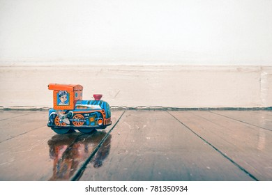 old tin toy train on a wooden floor with reflection
