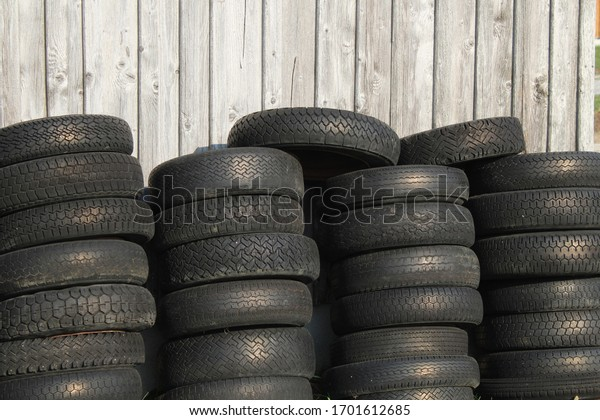 Old tires in front of a wooden wall