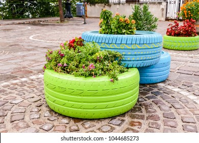 Old tires that are painted in assorted colors and used for a flower planter, modern garden