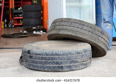 Old tires.Old used car tires in secondary car parts shop garage.Used car tires pile in the tire repair shop yard.Column stack of old used car tires in secondary car parts shop garage.
