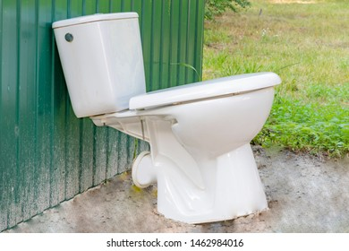 The old toilet is near the trash