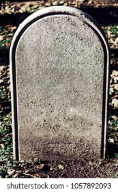 An old tombstone marks a grave in a graveyard.