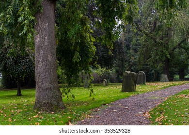 Old  tombstones among the trees in autumn park in Germany