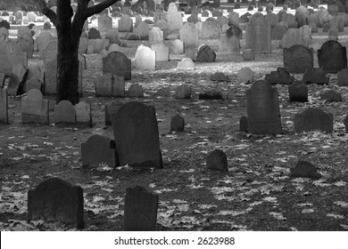 old tombstones mingle with the fallen leaves on a winter's day in the granary cemetery in boston massachusetts