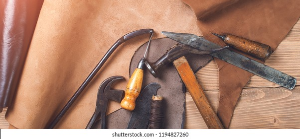 Old tools and leather at cobbler workplace. Shoemaker's work desk. Flat lay, top view. Set of leather craft tools on wooden background. Shoes maker tools. Pieces of brown leather. Shoemaker's shop