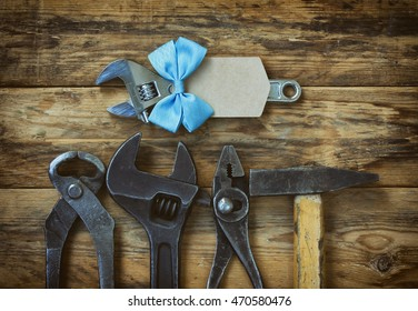 old tools, new wrench with blue ribbon and paper tag, fathers day greeting card