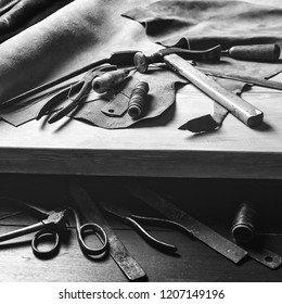 Old tools at table. Pieces of leather at cobbler workplace. Shoemaker's work desk. Leather craft tools on wooden background. Shoemaker tools. Shoemaker's shop. Black and white. Cobbler workmanship