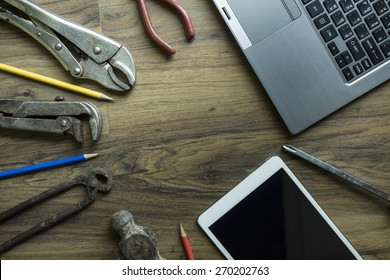 Old tools , tablet, computer on a wooden table