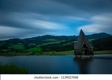 an old top part of a clocktower in a lake as an artwork