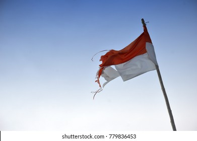 old and torn ripped Indonesia's flag against blue sky